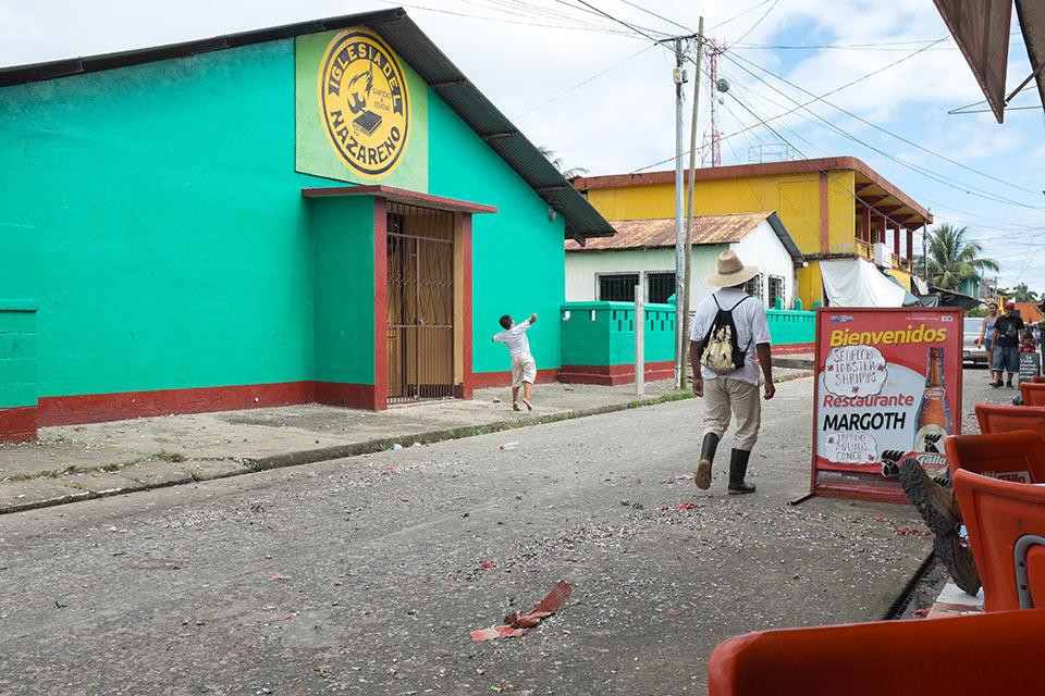 Kid throwing firecrackers in the street, Livingstone, Guatemala